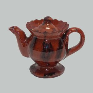 2818447, Miniature redware teapot, shaped top rim footed base, manganese decoration. $4,800