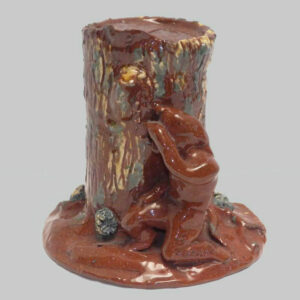 30-20247, Rare PA redware figural penny bank, indian behind tree stump, yellow and blue slip. Image