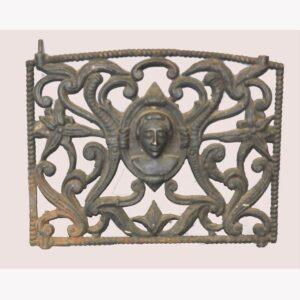 22-4623, Cast iron grate, wonderful folk art portrait flanked by ornate scrolled designs, 19th century. $2,400