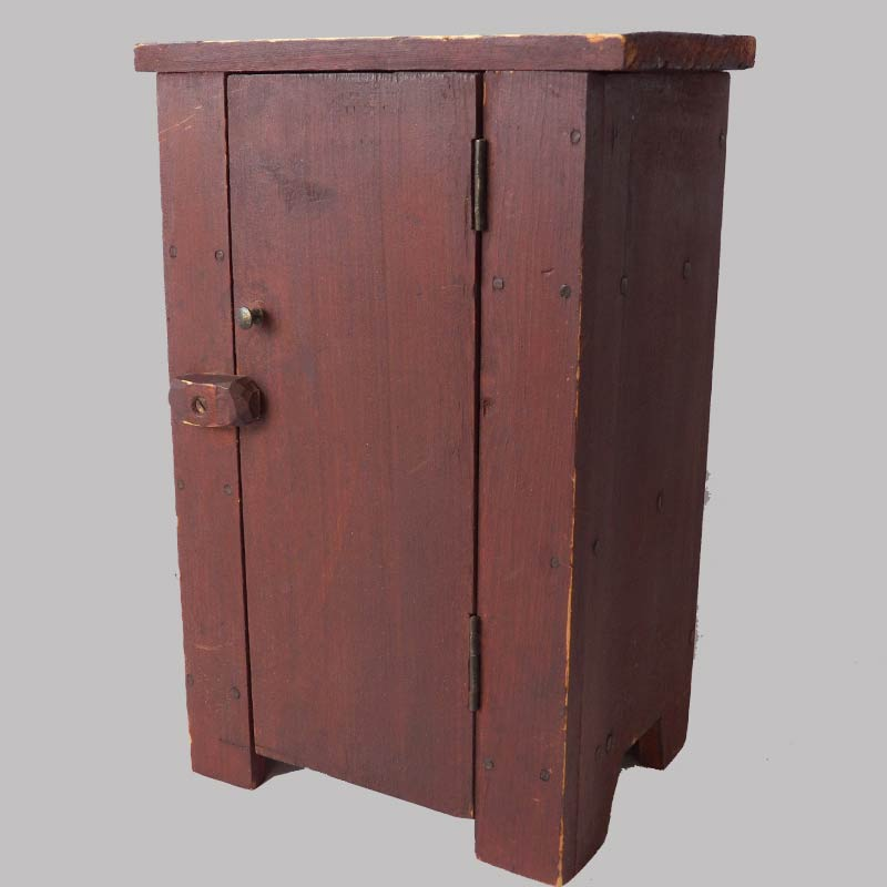 16-27574, Miniature or child's country cupboard, single plank door original red, mid 19th century. $775