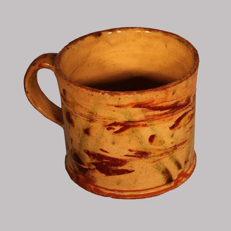 "22-4549x, Exceptional PA Redware pottery handled mug, yellow slip red and green decoration. Early 19th century, 3""H. $3,800"