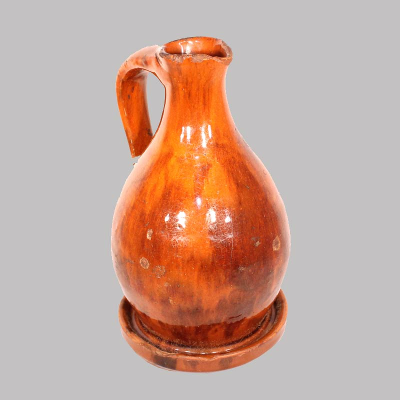 "25-12825x, Rare Redware handled syrup pitcher with saucer base, manganese decorated, Pro. New England, 7"" H. $1,450"