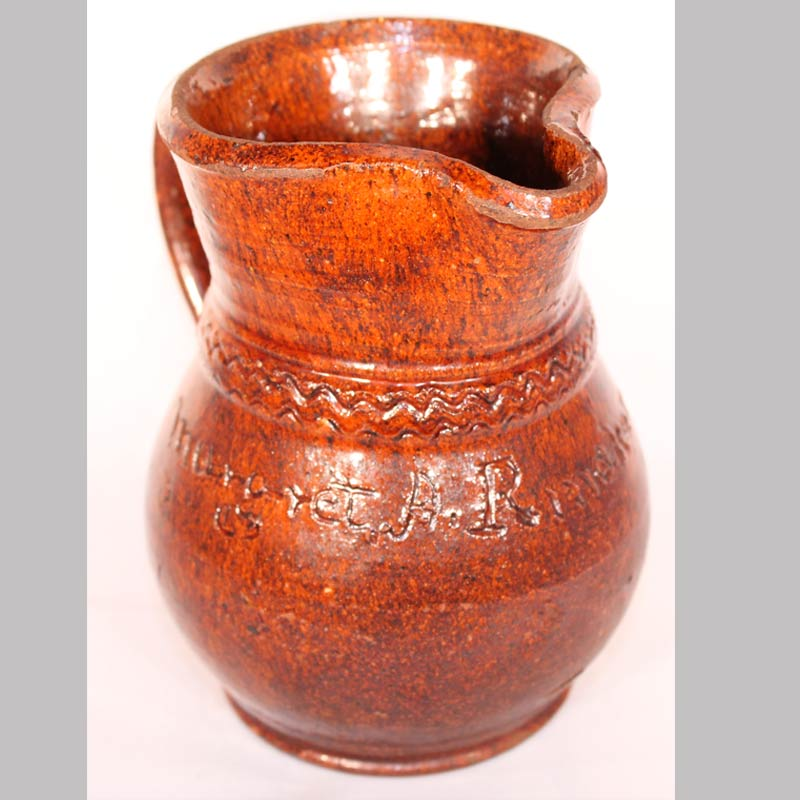 "22-4829, Redware pottery pitcher with incised name Margart A. Rinaker, good form coggled band, 5 1/2"" H. $1,200"