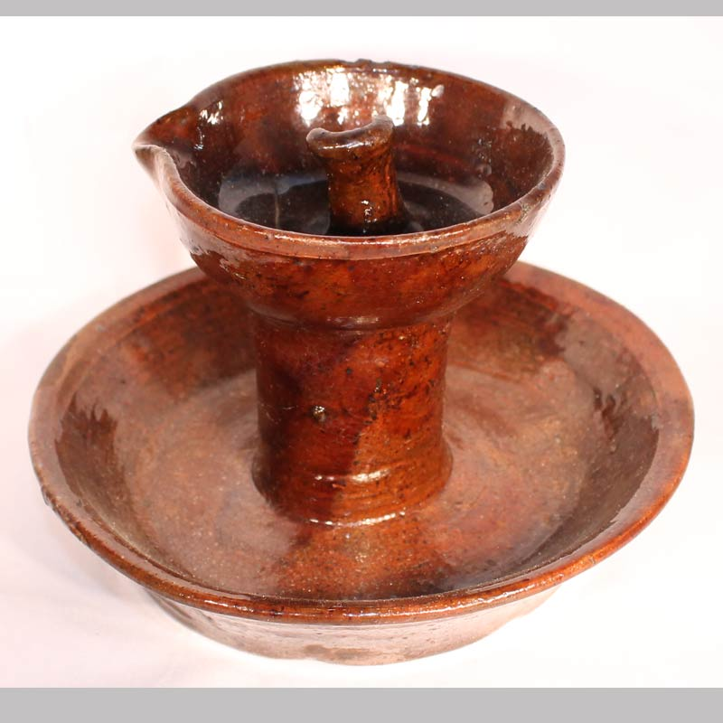 "14-23966, PA Redware saucer base fat lamp, rim nick. 4 1/2"" high by 6"" wide. $1,200"