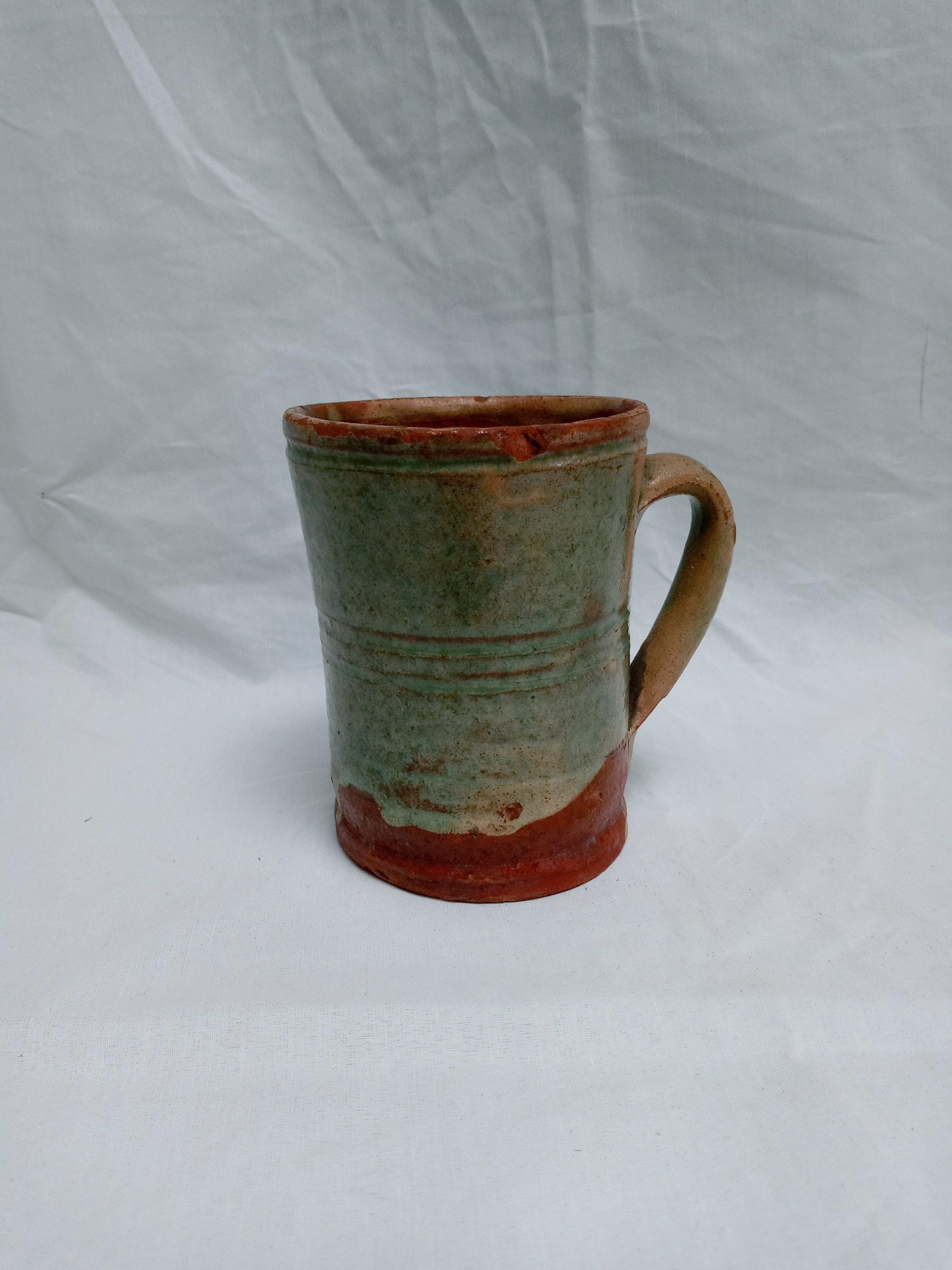 200-35624 Redware Pottery Handled Mug, yellow, green overall slip glaze, minor rim wear. Image